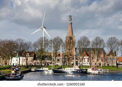 Medemblik, The Netherlands, October 21, 2018: Europe's largest wind turbine and Bonifatius Church, seen from across one of the old town's harbours