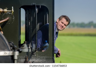 MEDEMBLIK, NETHERLANDS - SEPTEMBER 7, 2014: The train driver of vintage steam train looking at the window