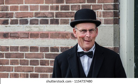 MEDEMBLIK, NETHERLANDS - SEPTEMBER 7, 2014: Funny dutch man with black bowler hat and glasses posing on brick wall background