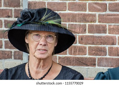 MEDEMBLIK, NETHERLANDS - SEPTEMBER 7, 2014: Funny old fashioned dressed dutch woman sit on brick wall background