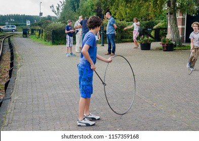 MEDEMBLIK, NETHERLANDS - SEPTEMBER 7, 2014: The boy play with metal wheel, an old game.