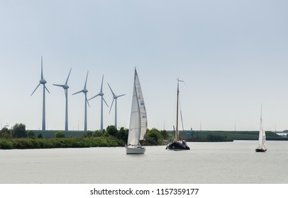 MEDEMBLIK, NETHERLANDS - SEPTEMBER 7, 2014: Beautiful yachts sailing on wind turbines background at IJsselmeer bay. Netherlands