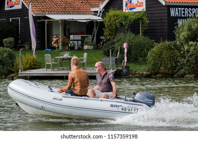 MEDEMBLIK, NETHERLANDS - SEPTEMBER 7, 2014: Two guys riding on an motorized inflatable boat at Medemblik harbor