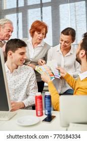 Media designer in design workshop choosing from color palette
