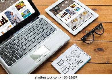 media, internet, business and technology concept - close up of blog web page on laptop computer screen, tablet pc, notebook and eyeglasses on wooden table