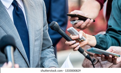 Media Interview - journalists with microphones interviewing formal dressed politician or businessman.