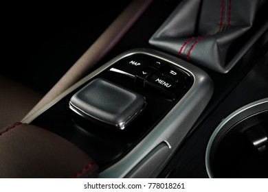 Media and navigation control joystick of a modern car on the dashboard. Car interior details. Red leather with stitch interior of the luxury modern car.