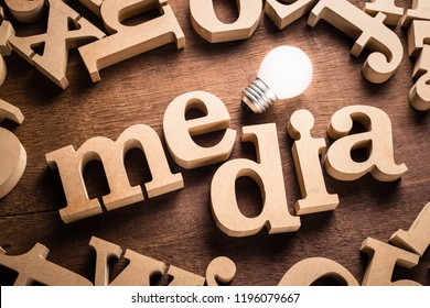 Media word in scattered wood letters with glowing white light bulb