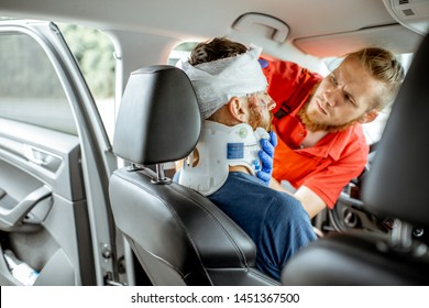 Medic applying bandage on the head of victim with serious damages sitting on the driver seat after the road accident. Providing emergency medical assistance