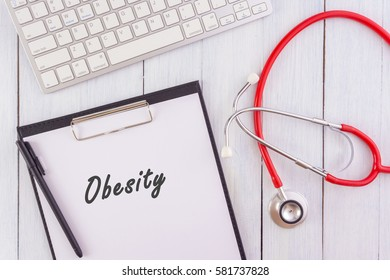 Medic concept.OBESITY written on note pad,stethoscope,keyboard on wooden table.white background.