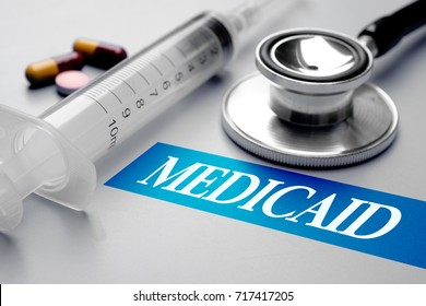 Medicaid, health concept. Stethoscope, syringe and pills on grey background. Selective focus image.