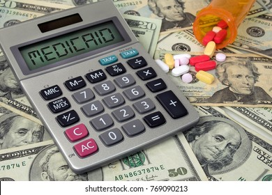 medicaid text on silver calculator with orange bottle of pills on American currency