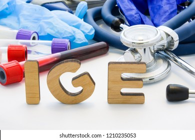 Medical abbreviation IGE in laboratory diagnostics. Letters, create words IGM, meaning Immunoglobulin E antibody, are surrounded by test tubes with blood, stethoscope and other medical equipment