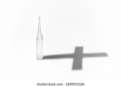 Medical ampoule with vaccine on a white background. Ampoule shadow in the shape of a cross. Unlicensed vaccine concept, medicine with side effects, dangerous treatment