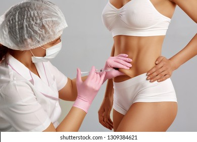Medical anti cellulite treatment of belly, making by professional surgeon. Woman with beautiful body, wearing white underwear, getting rejuvenating and lifting correction of skin.