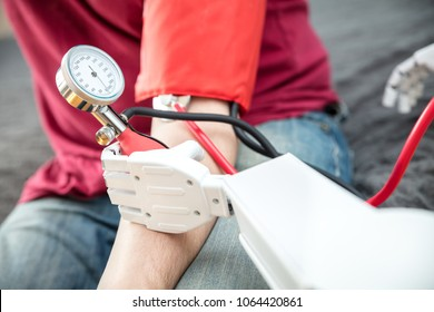 medical assistance robot is checking the blood pressure of a male patient, while using a stethoscope