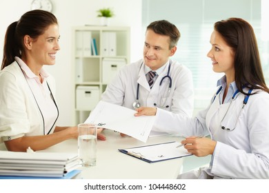Medical assistant giving the prescription to the smiling patient