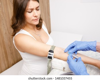 Medical assistant or nurse taking a blood sample from arm vein of pregnant woman with a vacutainer. Venipuncture or venepuncture procedure concept
