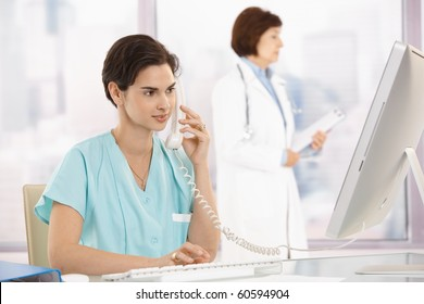 Medical assistant sitting at desk, talking on landline phone, using computer, doctor in background.?