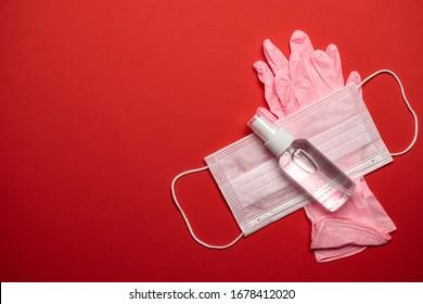 Medical background red. Medical surgical mask, sanitizer gel and lab gloves on Virus protection equipment. Dangerous illness corona virus. Novel Coronavirus 2019-nCoV