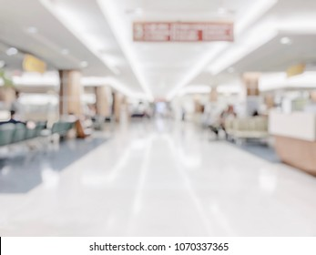 Medical blur background clinic healthcare service center or hospital in OPD - outpatient department blurry interior white waiting lobby room with patient's , doctors, nurse staff station counter area
