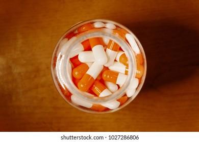 Medical Bottle Full Of Orange-white Pills From Above View
