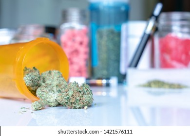 Medical cannabis image with selective focus on a chunk of dried flower and other marijuana products soft focus in the background, including edibles, vape pen, loose marijuana on a rolling paper