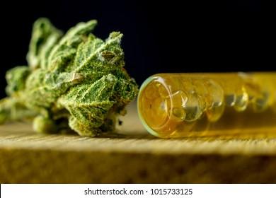 Medical Cannabis Oil - marijuana flower and cannabis oil on the fresh natural oak wood.