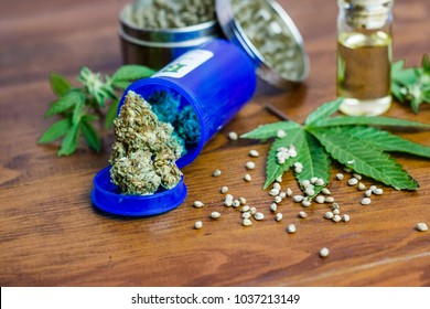 Medical cannabis on wood table with an oil extract, seeds and leafs.