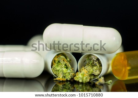 Medical Cannabis pills - marijuana tablets, concept on the black mirror background.