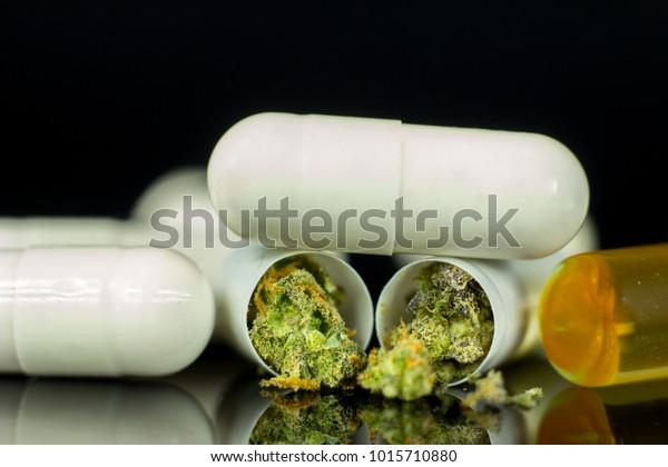 Medical Cannabis pills - marijuana tablets, concept on the black mirror background.