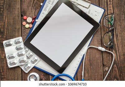 Medical card of patient, stethoscope, tablet and pills on wooden table top view