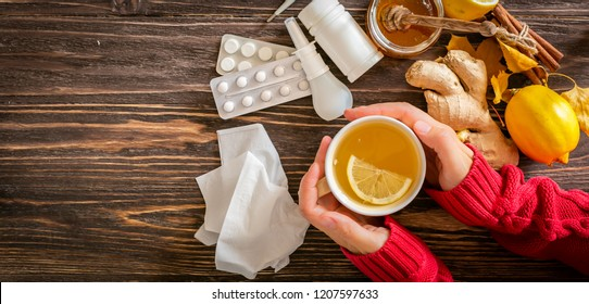 Medical care concept - hands holding cup with ginger honey and lemon tea with drugs, pills and spray on wood background