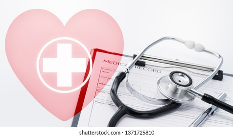 Medical care and emergency concept image. Pink heart icon with cross. Stethoscope on medical record.