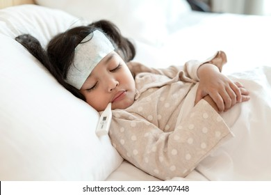 Medical check up and treatment concept. Mother is measure the temperature of little Asian kid girl. Sick child with fever and illness in bed.