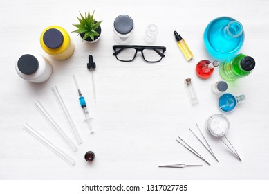 Medical, chemistry or pharmacy background. Laboratory table with a various chemical reagents, syringe and jars background with copy space. Flat lay.