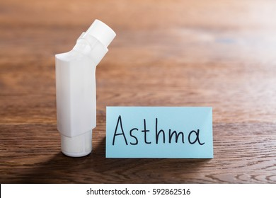 Medical Concept Of Asthma With An Inhaler On Wooden Desk