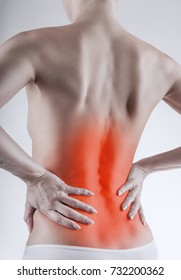 Medical concept. Close-up of a woman's back with backache against a light background