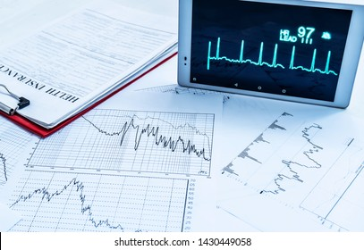 Medical concept. Health insurance blank and cardiogram computer expertise.