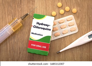 Medical Concept - Hydroxychloroquine medicine box with thermometer, syringe and pills