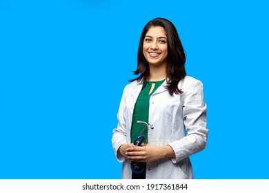 Medical concept of Indian beautiful female doctor in white coat with stethoscope, waist up. Medical student. Woman hospital worker looking at camera and smiling, studio, blue background