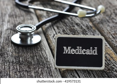 Medical Concept- Medicaid word written on blackboard with Stethoscope on wood background