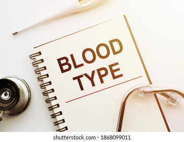 Medical concept. Notebook with word BLOOD TYPE on white desk with stethoscope and thermometer