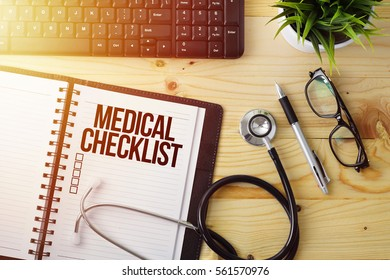 Medical Concept - Notepad written MEDICAL CHECKLIST with checkbox on wooden desk with a stethoscope, pen, keyboard, flower pot and a glasses with sun flare effect