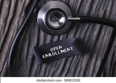 Medical Concept- OPEN ENROLLMENT word written on label tag with Stethoscope on wood background
