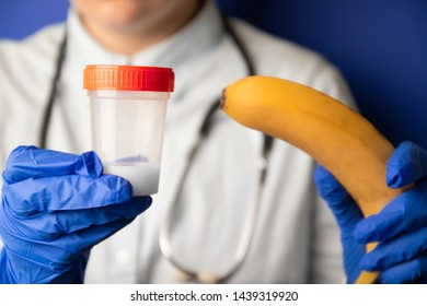 Medical concept of sperm testing, artificial insemination. Female doctors hands in medical blue gloves holding a plastic container with sperm and a banana