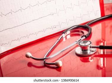 Medical concept. Stethoscope and heart rate cardiogram diagnostic on red background.