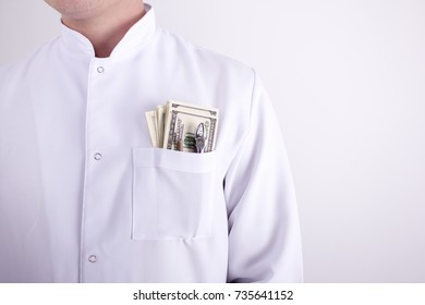 Medical concept. Stomatology. The man in the medical dressing gown and money in his pocket
