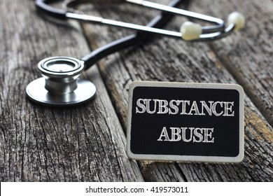 Medical Concept- SUBSTANCE ABUSE word written on blackboard with Stethoscope on wood background
