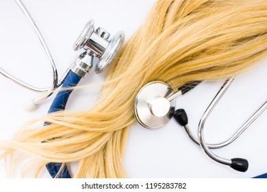 Medical concept in trichology, dermatology and hair examination. Curl or lock of blonde hair of patient  is surrounded by two heads of stethoscopes, which examined it top view